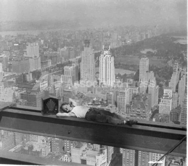 operaio che dorme sul grattacielo