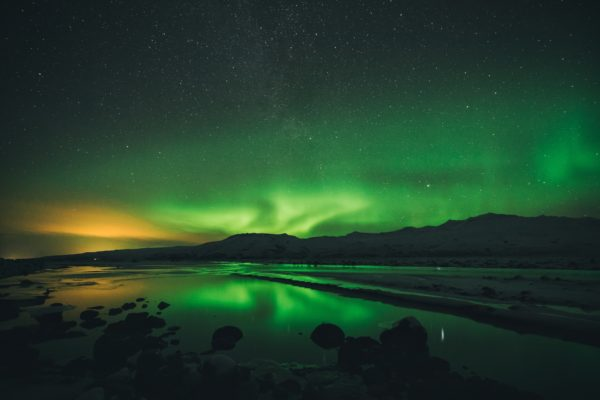 Long exposure picture capturing northern lights and light pollution of the nearby town on the left. There is also a small glimpse of milky way on the top, but the best part is hidden under the horizon